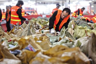 2013年电商双11大促后第二天,申通快递北京分拨中心的工作人员晚11时还在处理快件。今后,卖家在电商平台开店前,可能需要提交营业执照等证照信息。资料图片